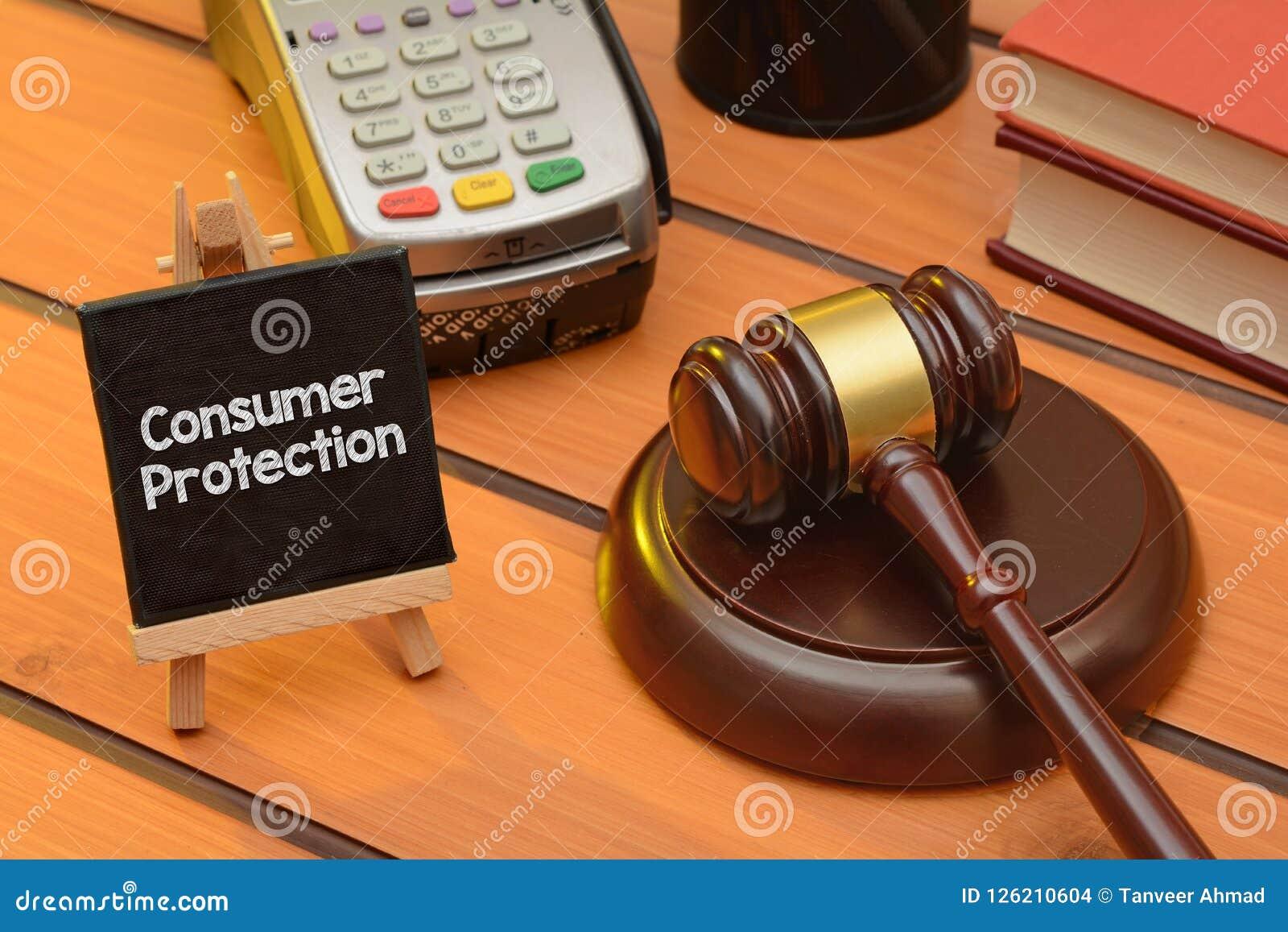 Tema de la protección al consumidor con el mazo de madera en la tabla, fondo de la ley