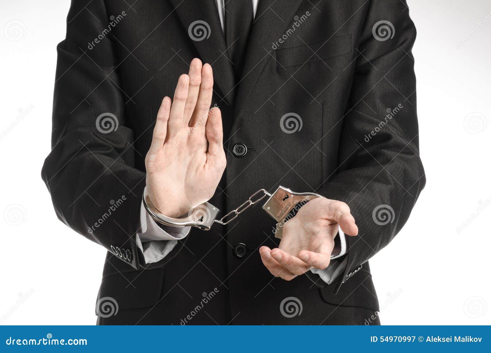 Tema di corruzione e di corruzione: uomo d affari in un vestito nero con le manette sulle sue mani su un fondo bianco in studio i