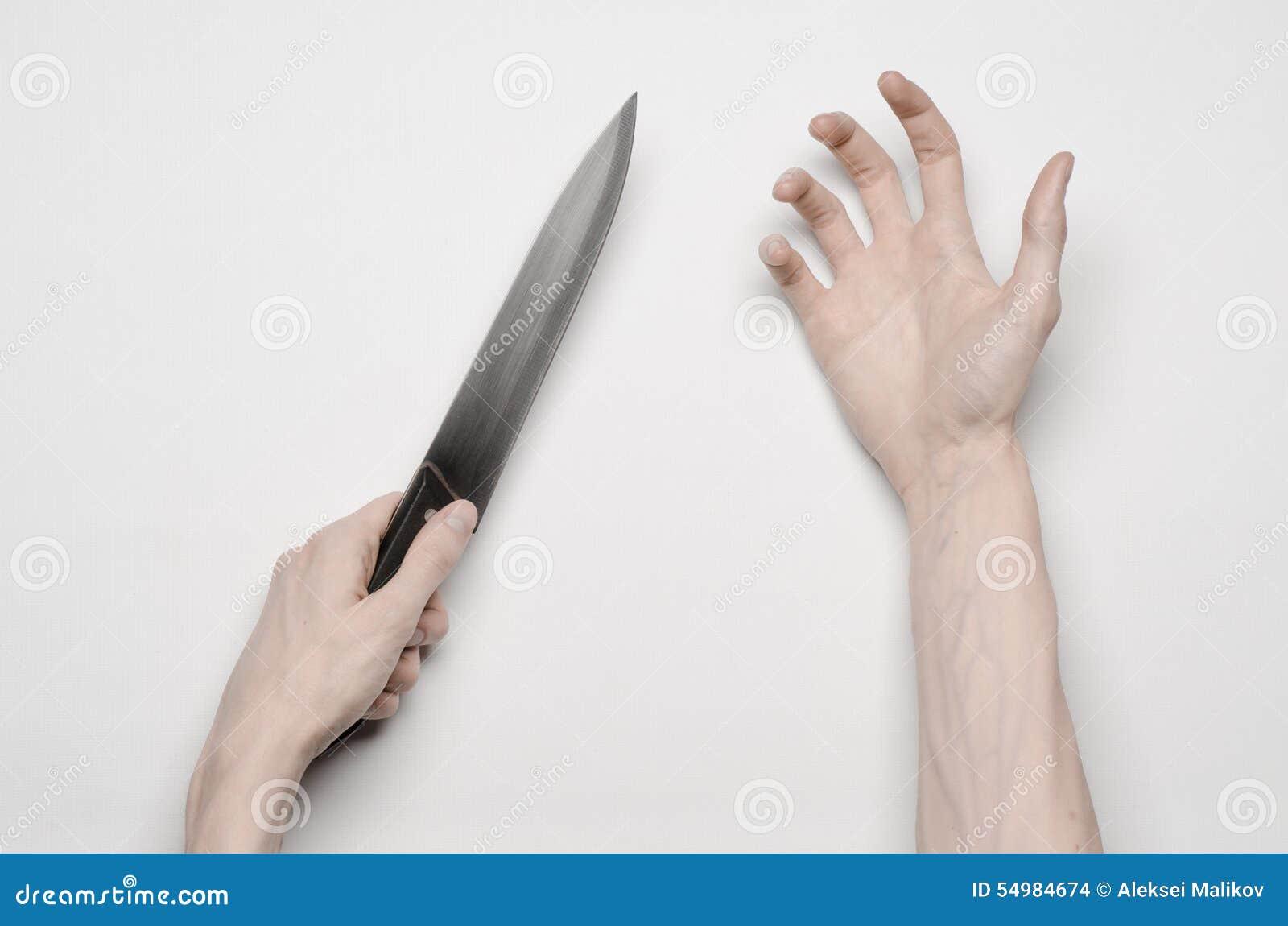 Tema do assassinato e do Dia das Bruxas: A mão que alcança para uma faca, uma mão humana de um homem que mantém uma faca isolada