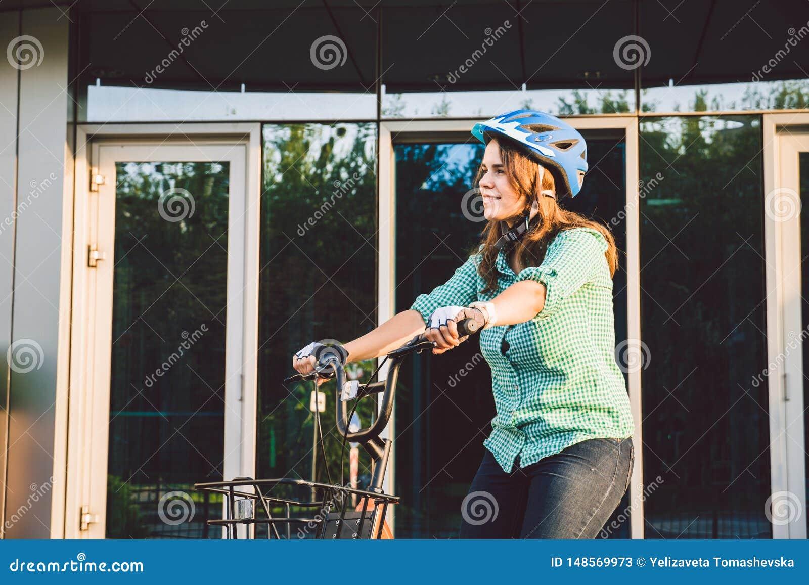Tema som arbetar p? cykeln En ung Caucasian kvinna ankom p? den milj?v?nliga transportcykeln till kontoret Flicka i a