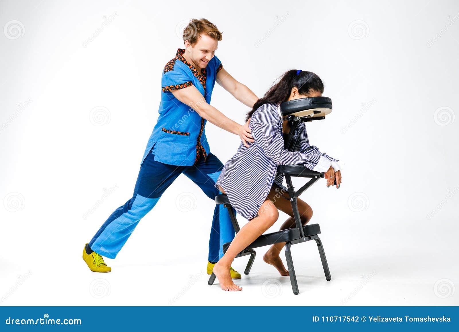 Temamassage och kontor En ung man med att le terapeuten i blåttdräkt gör tillbaka och halsmassagen för arbetare för den unga kvin