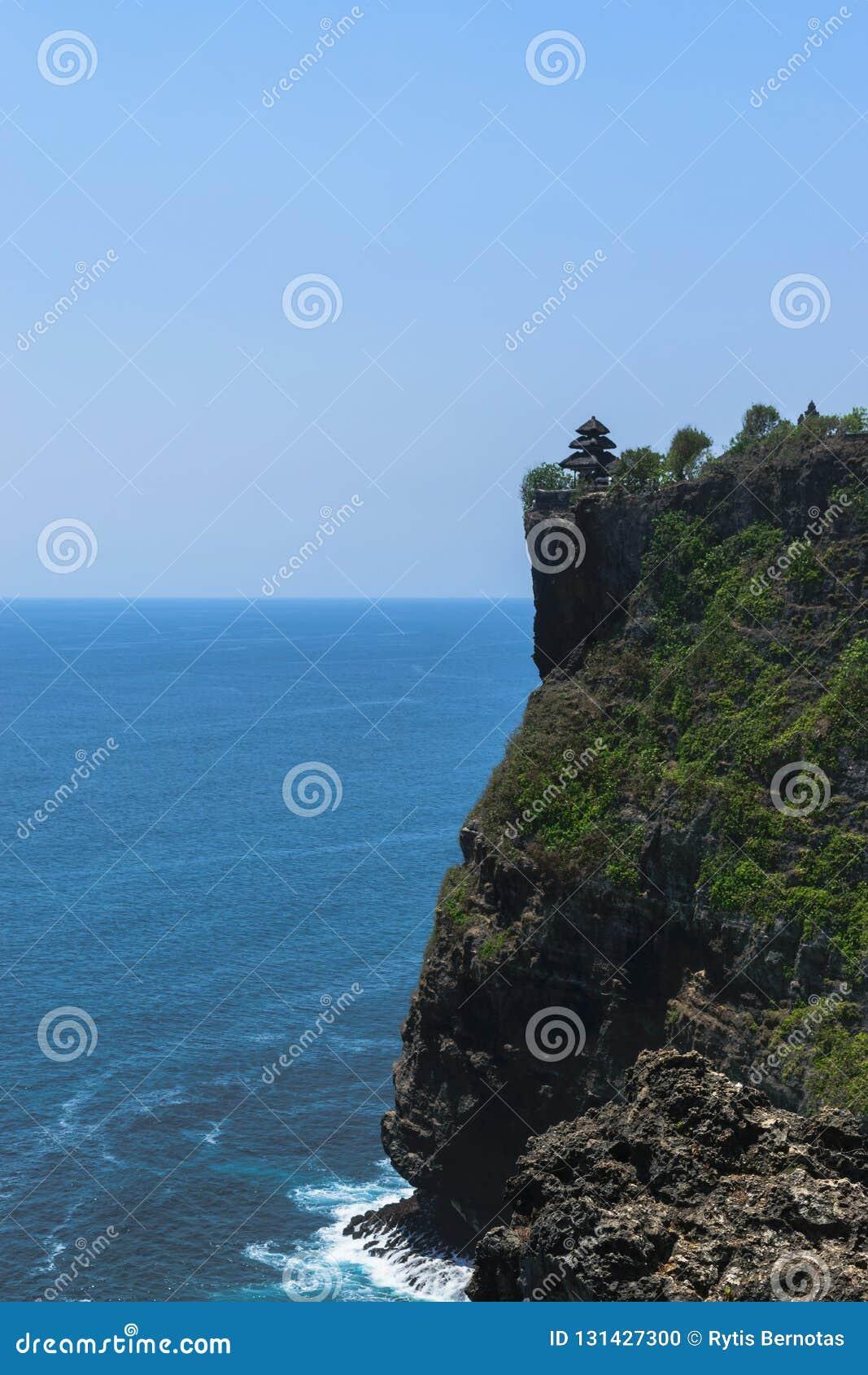 Tempel för Pura luhuruluwatu på klippan med härlig sikt av det blåa indiska havet i Bali, Indonesien