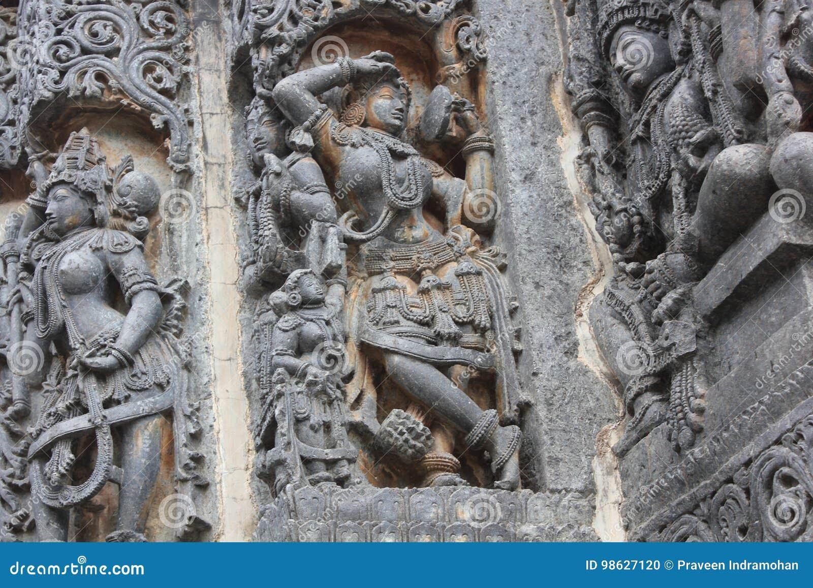 Hoysaleswara Temple wall carved with sculpture of Darpana Sundari beautiful lady with mirror
