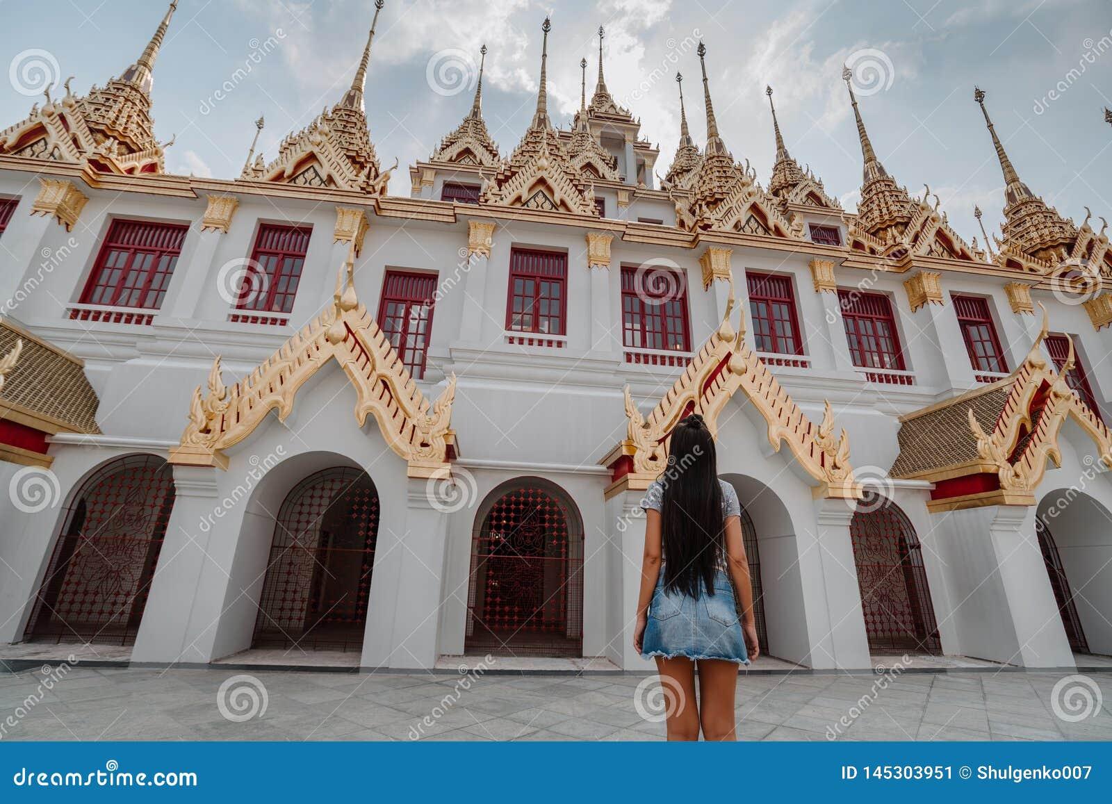 Templo asiático fabuloso, místico, budista com pagodes e estátuas Mulher impressa com a beleza do lugar