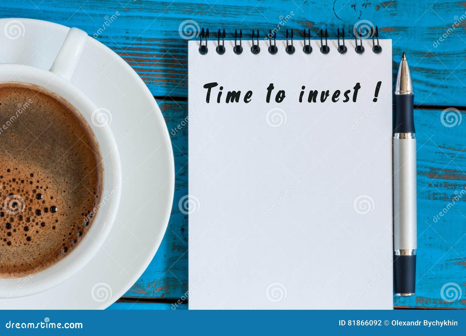Tempo di investire - avviso in blocco note alla tavola di legno blu con la tazza da caffè di mattina Risparmio, concetto di affar
