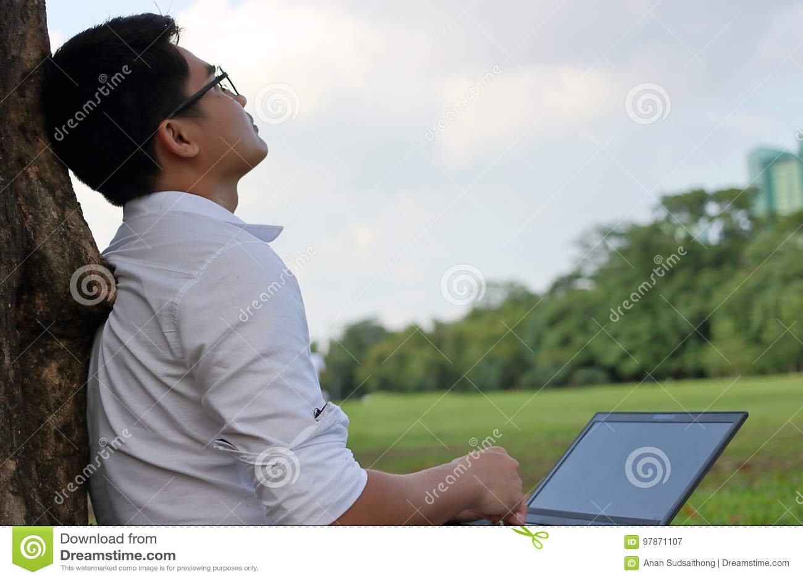 Tempo di riposo Giovane asiatico che esamina il cielo dopo il lavoro contro il suo computer portatile