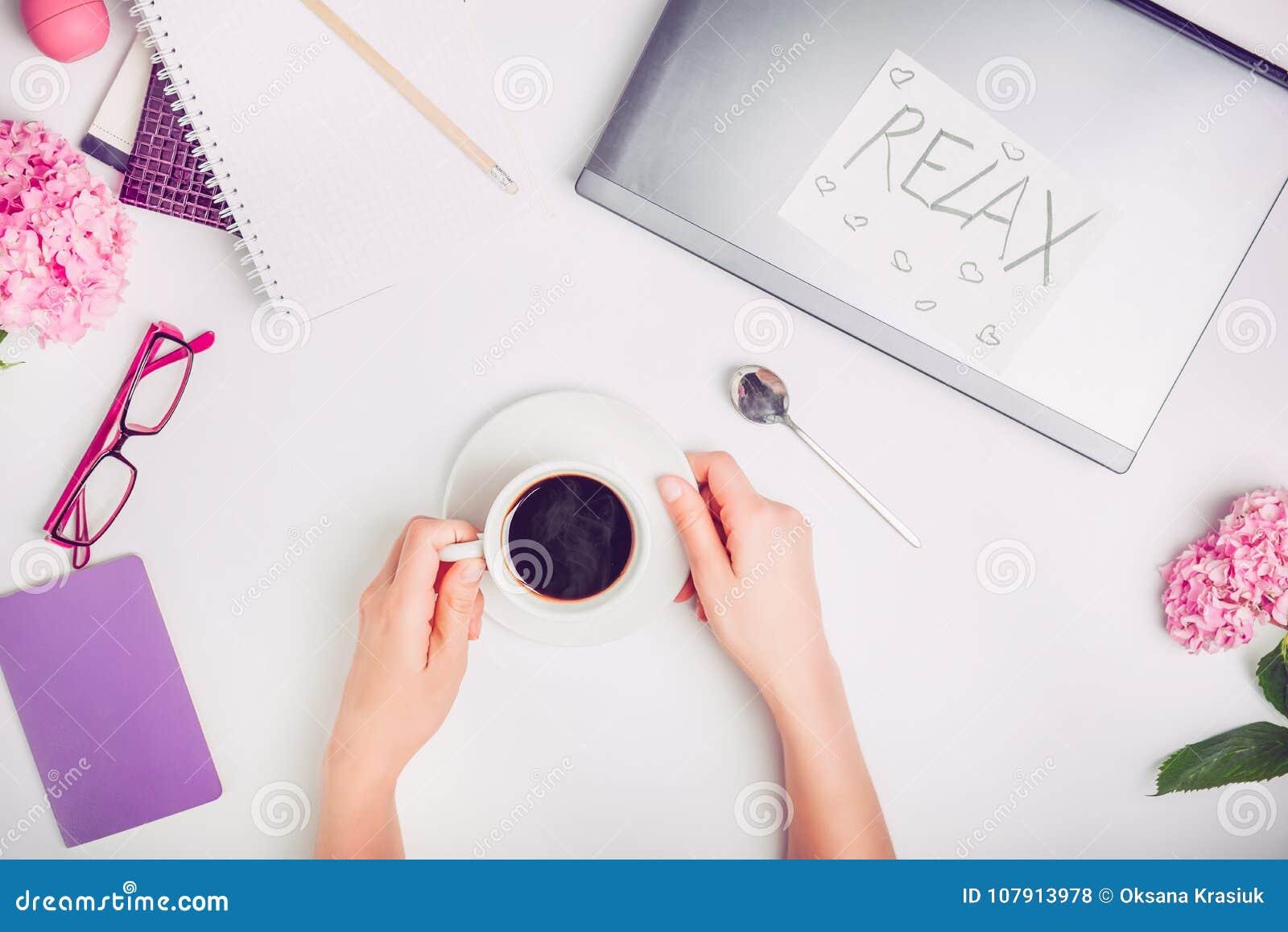 Tempo no espaço de trabalho - mãos fêmeas da ruptura de café com a xícara de café na mesa de escritório de trabalho branca com po