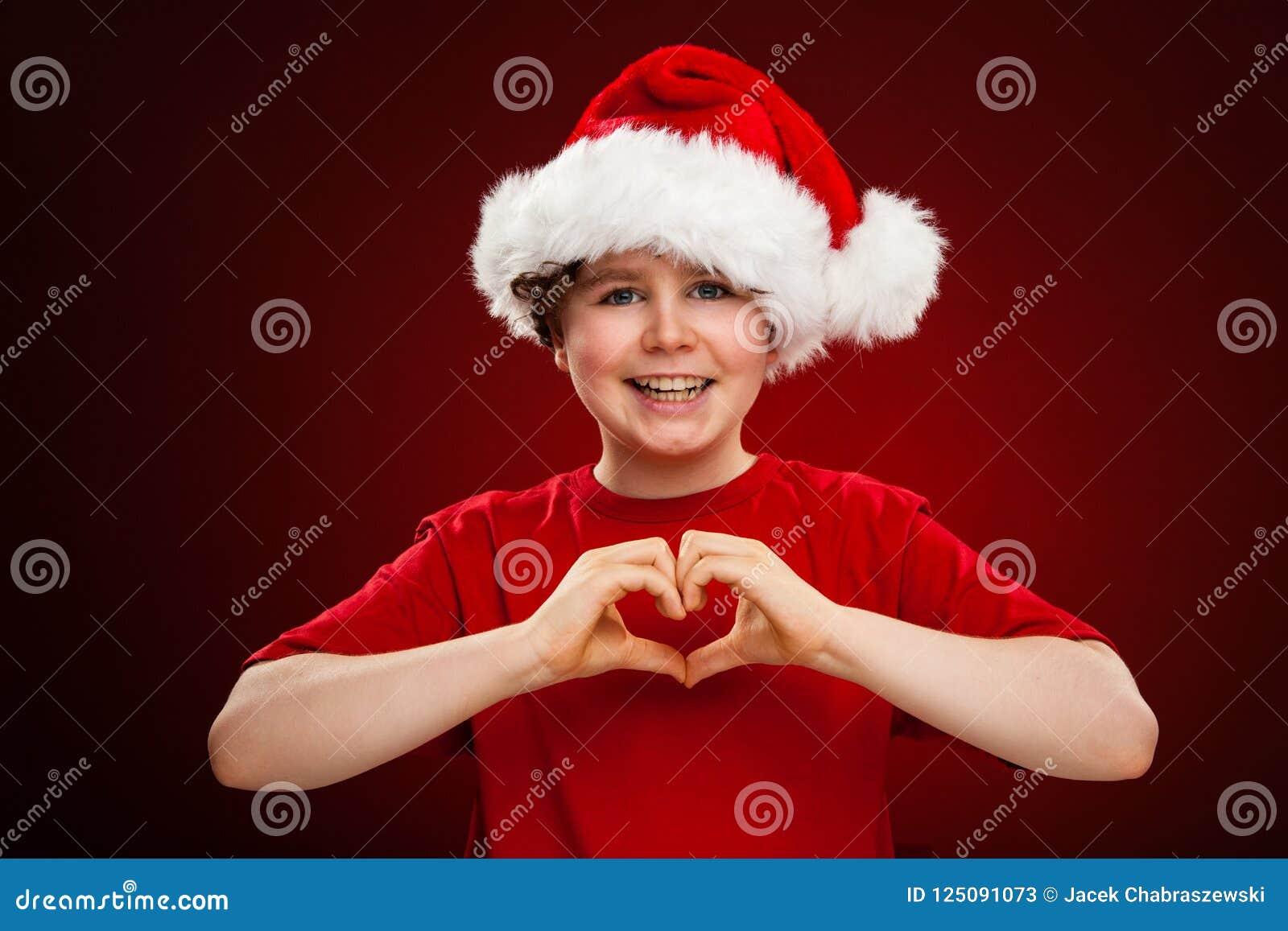 Temps de Noël - garçon avec Santa Claus Hat montrant le signe de coeur