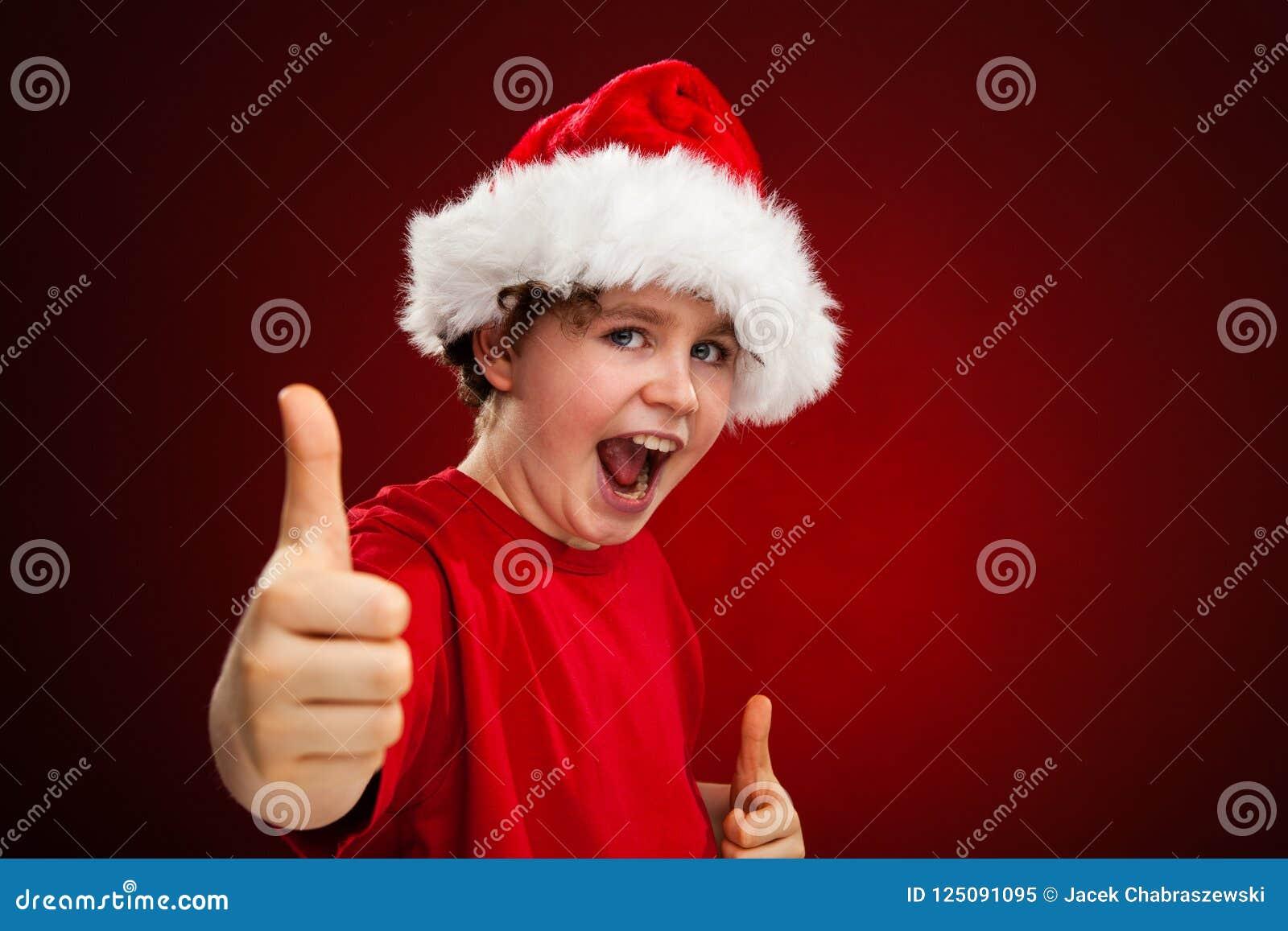Temps de Noël - garçon avec Santa Claus Hat montrant le signe correct