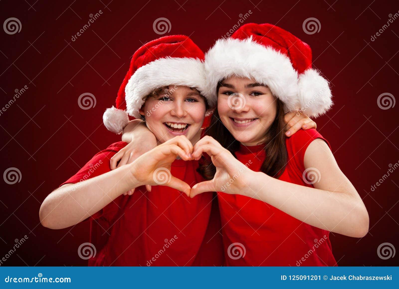 Temps de Noël - la fille et le garçon avec Santa Claus Hats montrant le coeur signent