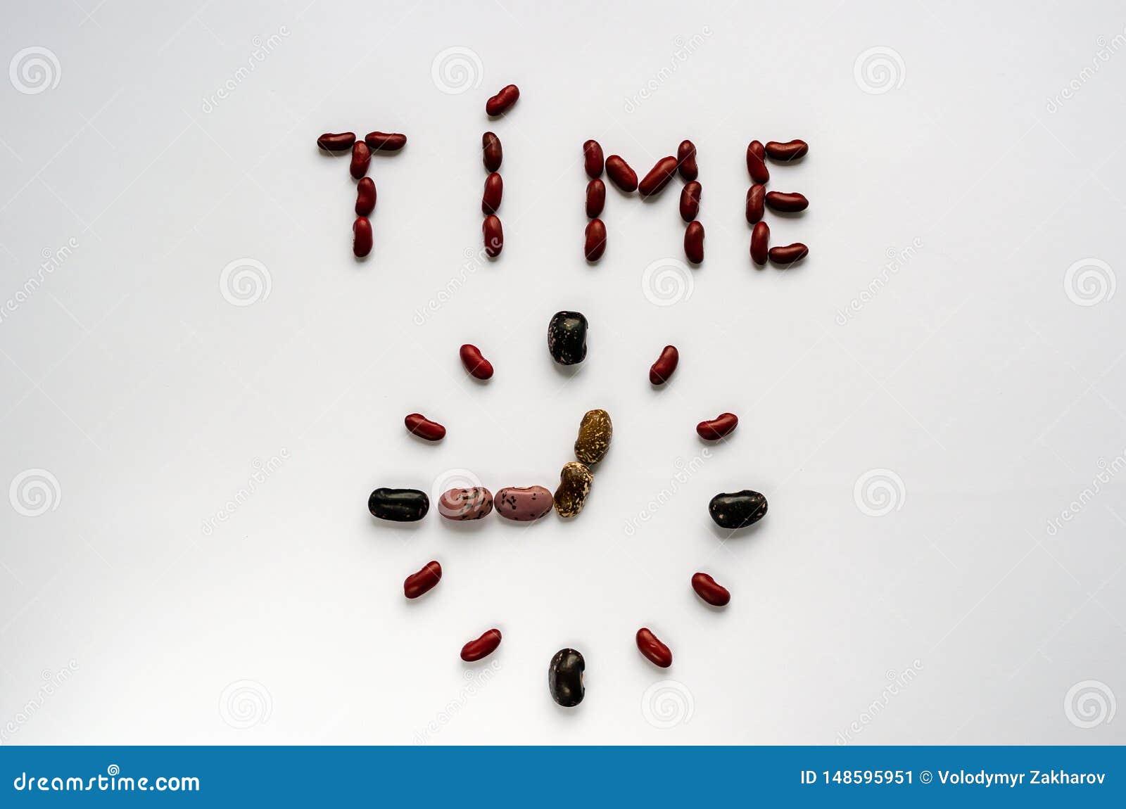 Temps de Word et visage d horloge form? hors des haricots nains color?s sur le fond blanc Concept sain de consommation