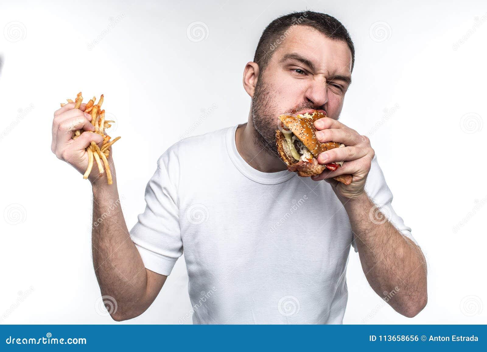 Ten facet jest bardzo zachwytem szybkie żarcie Gryźć dużego kawałek hamburger i trzyma pełną rękę francuscy dłoniaki