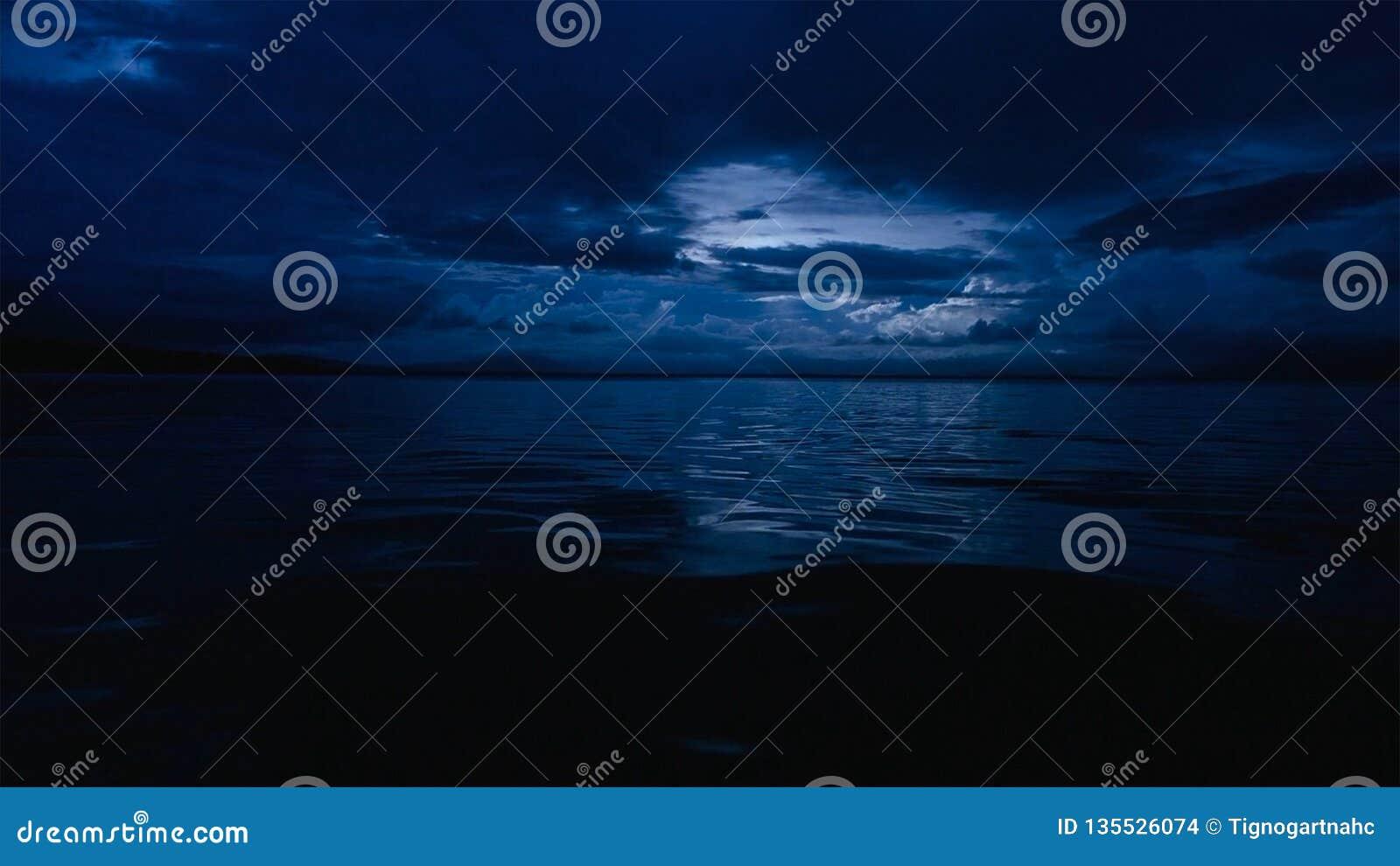 Ten fotografia głęboki błękitny moonlit ocean przy nocą z spokojnymi falami