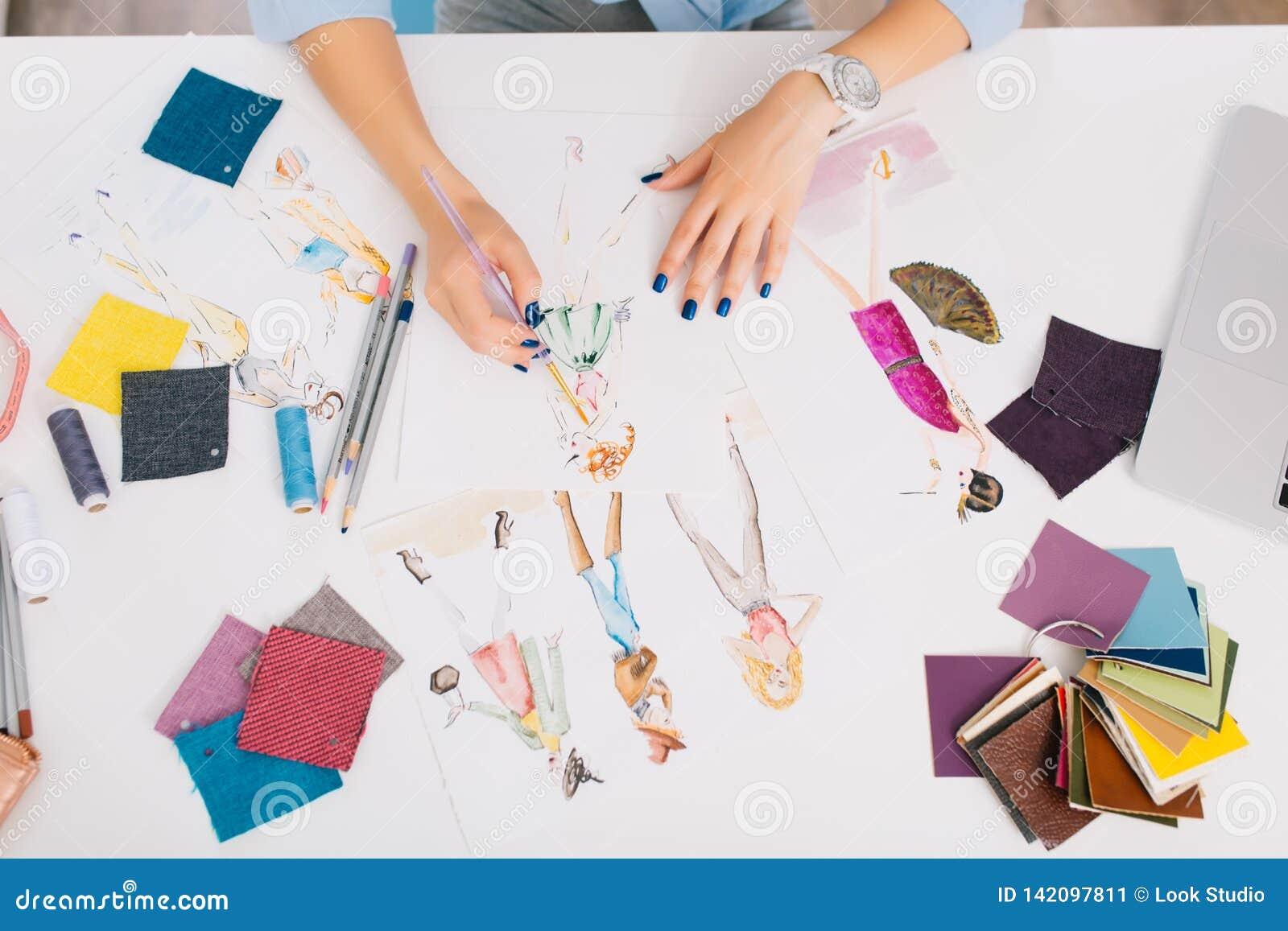 Ten obrazek opisuje procesy projektować odziewa Tam są ręki dziewczyna rysunku nakreślenia na stole