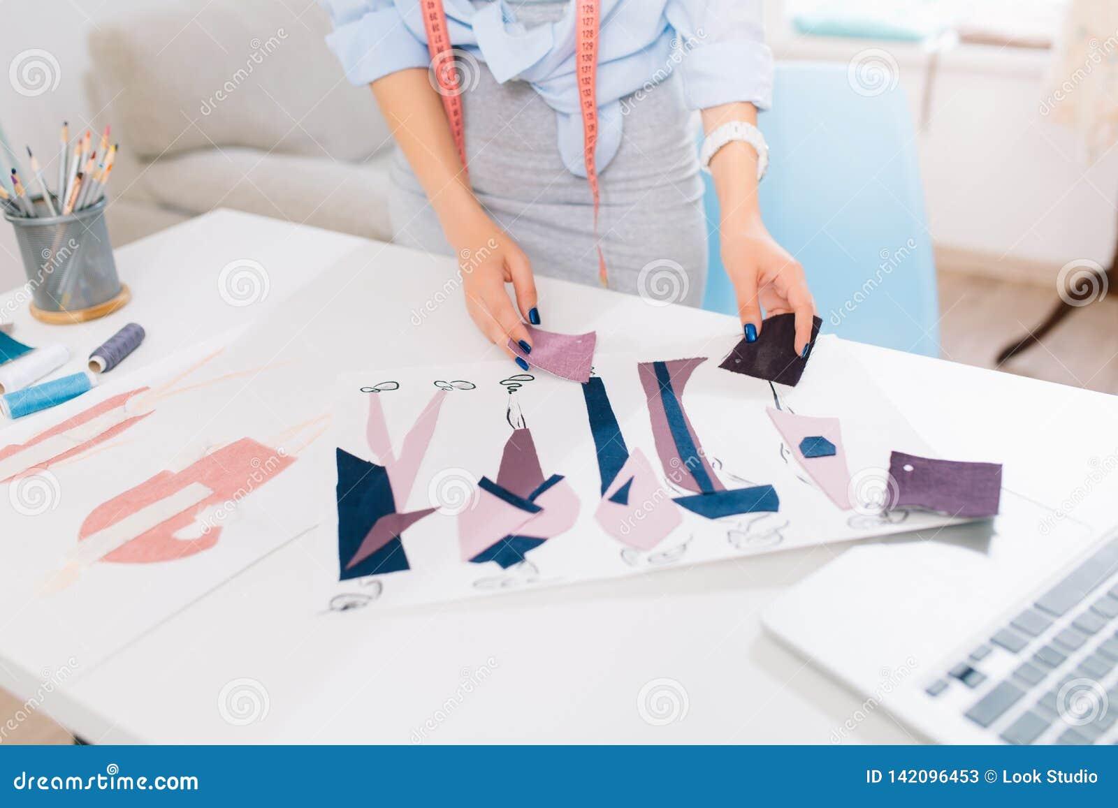Ten obrazek opisuje procesy projektować odziewa w warsztacie Tam są ręki dziewczyna szuka