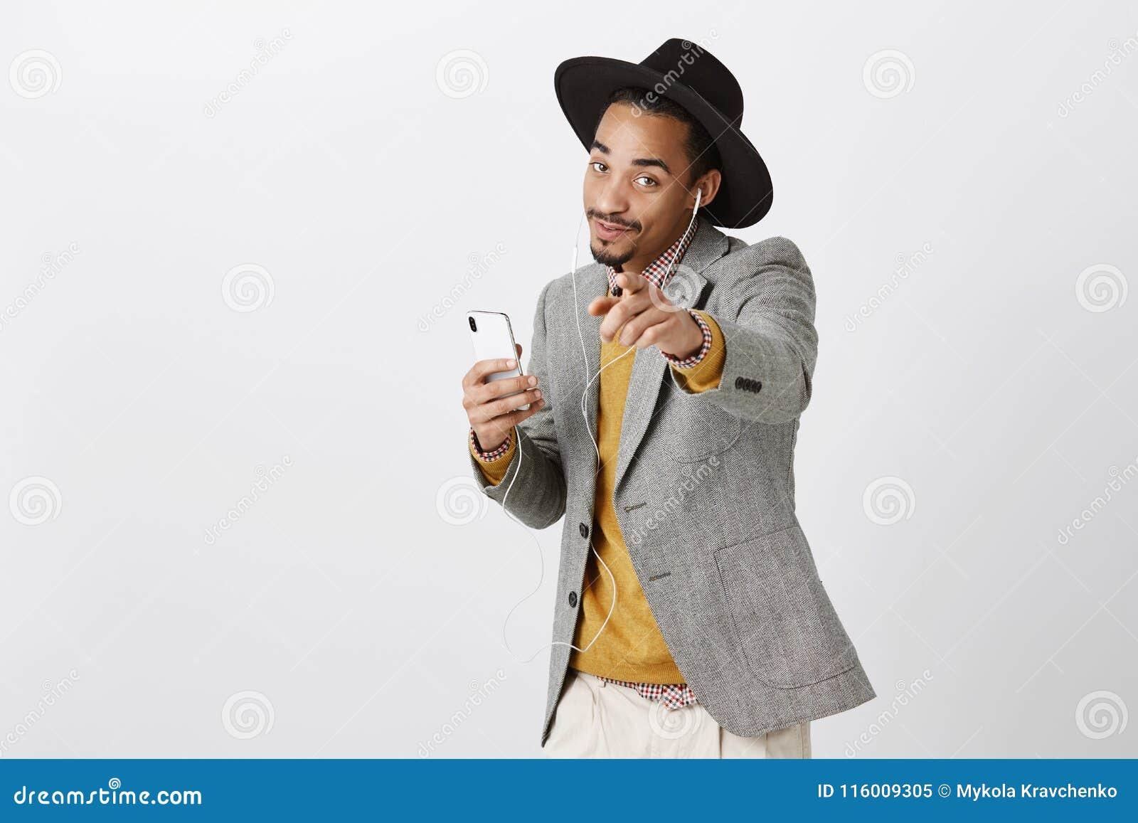 Ten piosenka jest o tobie Portret czarować ciemnoskórego eleganckiego ucznia w kapeluszowym i modnym stroju mienia smartphone