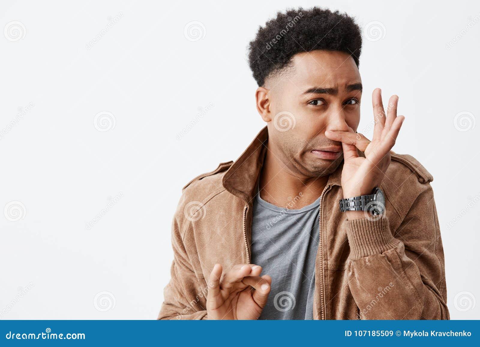 Ten wącha naprawdę bad Zamyka w górę portreta młody śmieszny ciemnoskóry mężczyzna z afro fryzury przymknięcia nosem z palcami