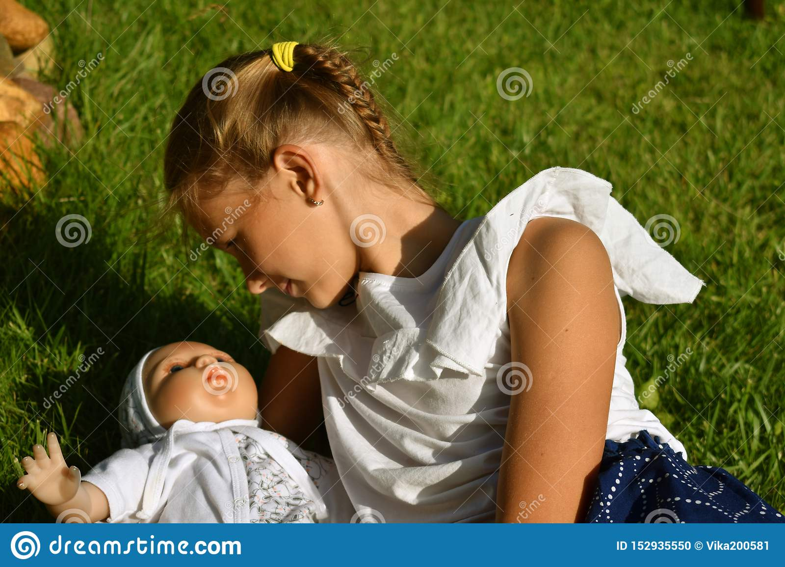 Beautiful little girl with a doll in the summer in a garden