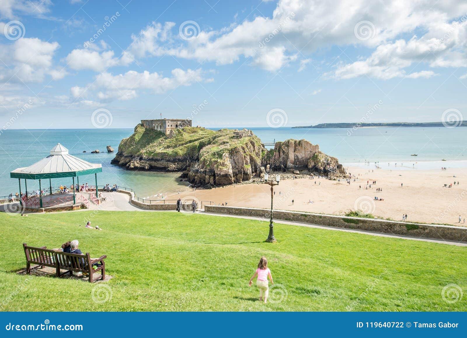 Tenby, Wales - Augustus 12, 2017: Mensen die van hun tijd bij Tenby-Kasteelruïnes en zandige strandmening genieten at low tide ti