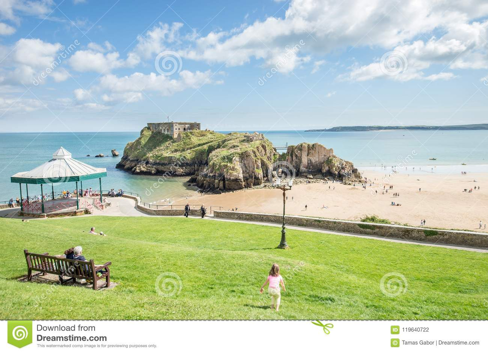 Tenby Walia, Sierpień, - 12, 2017: Ludzie cieszy się ich czas i piaskowatej plaży widok przy Tenby kasztelu ruinami przy niskim p
