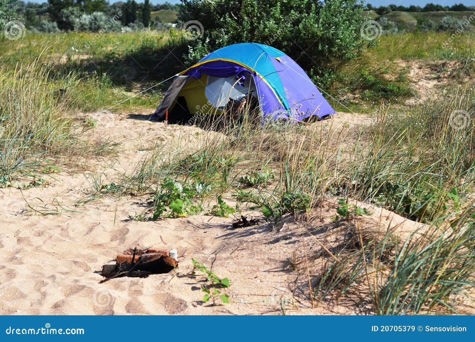 Tenda di campeggio blu che si leva in piedi sul puntello sabbioso. sul ...
