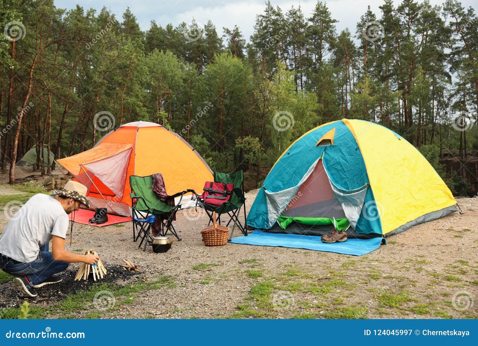Tende di campeggio vicine del falò di illuminazione dell uomo