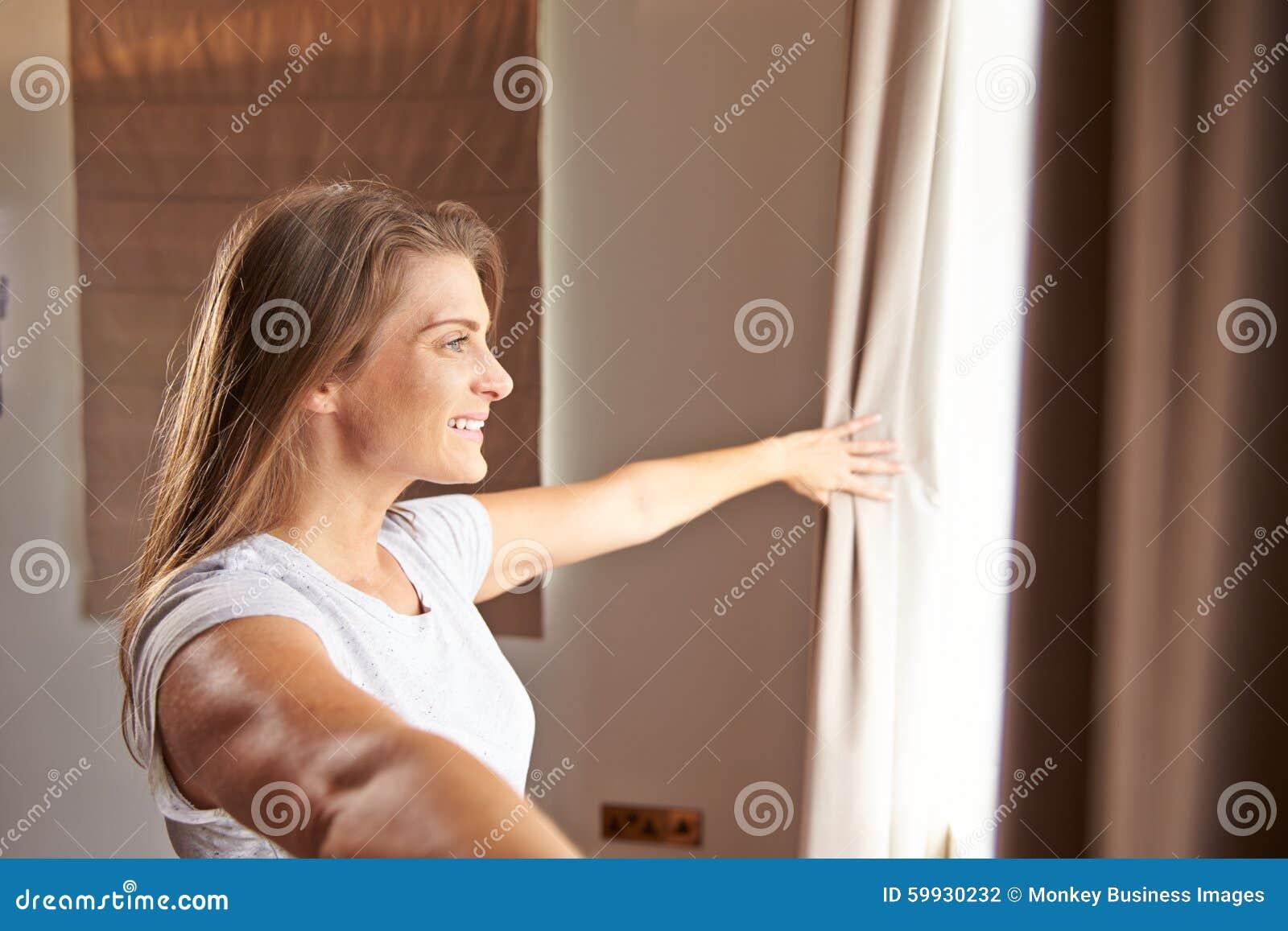 Tende facenti una pausa della finestra e di apertura della camera da letto della donna