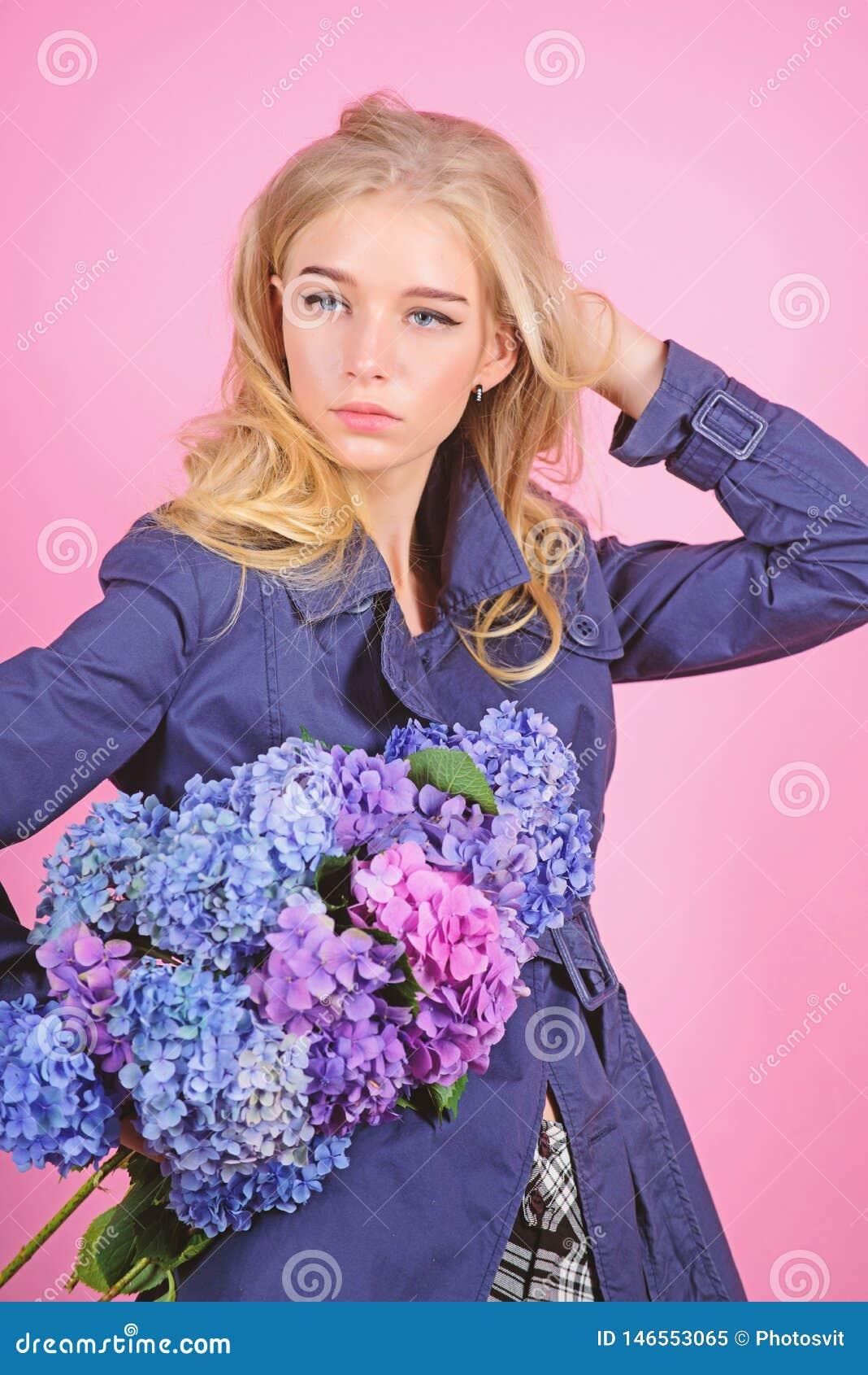 Tendencia de la moda de la trenca Capa de moda Debe tener concepto Ropa y accesorio Pelo rubio de la mujer que presenta la capa