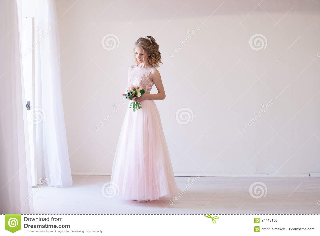 Tender bride in a white room before the wedding