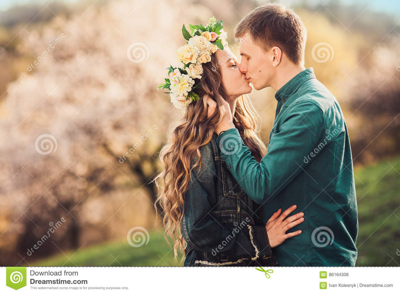 Tender kiss of young caucasian couple in sunset lights