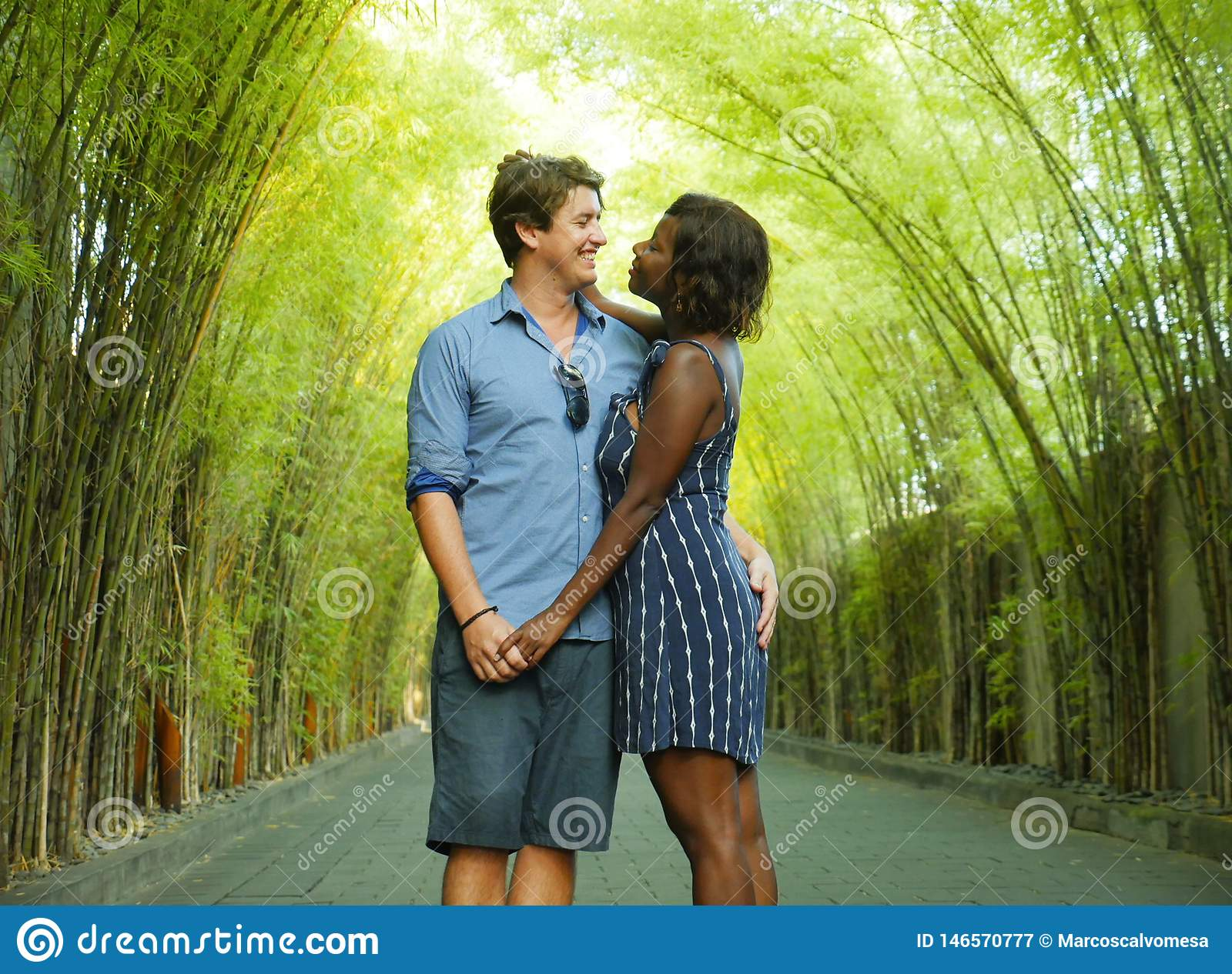 Tender mixed ethnicity couple cuddling outdoors with attractive black afro American woman and handsome Caucasian boyfriend or