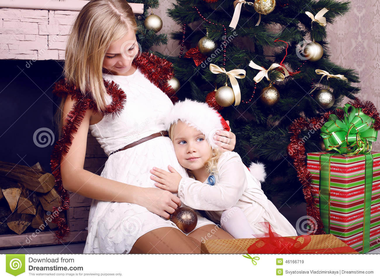 Adorable photo of happy family. pregnant mother with her little cute  daughter posing beside a decorated Christmas tree and presents b779e5a75