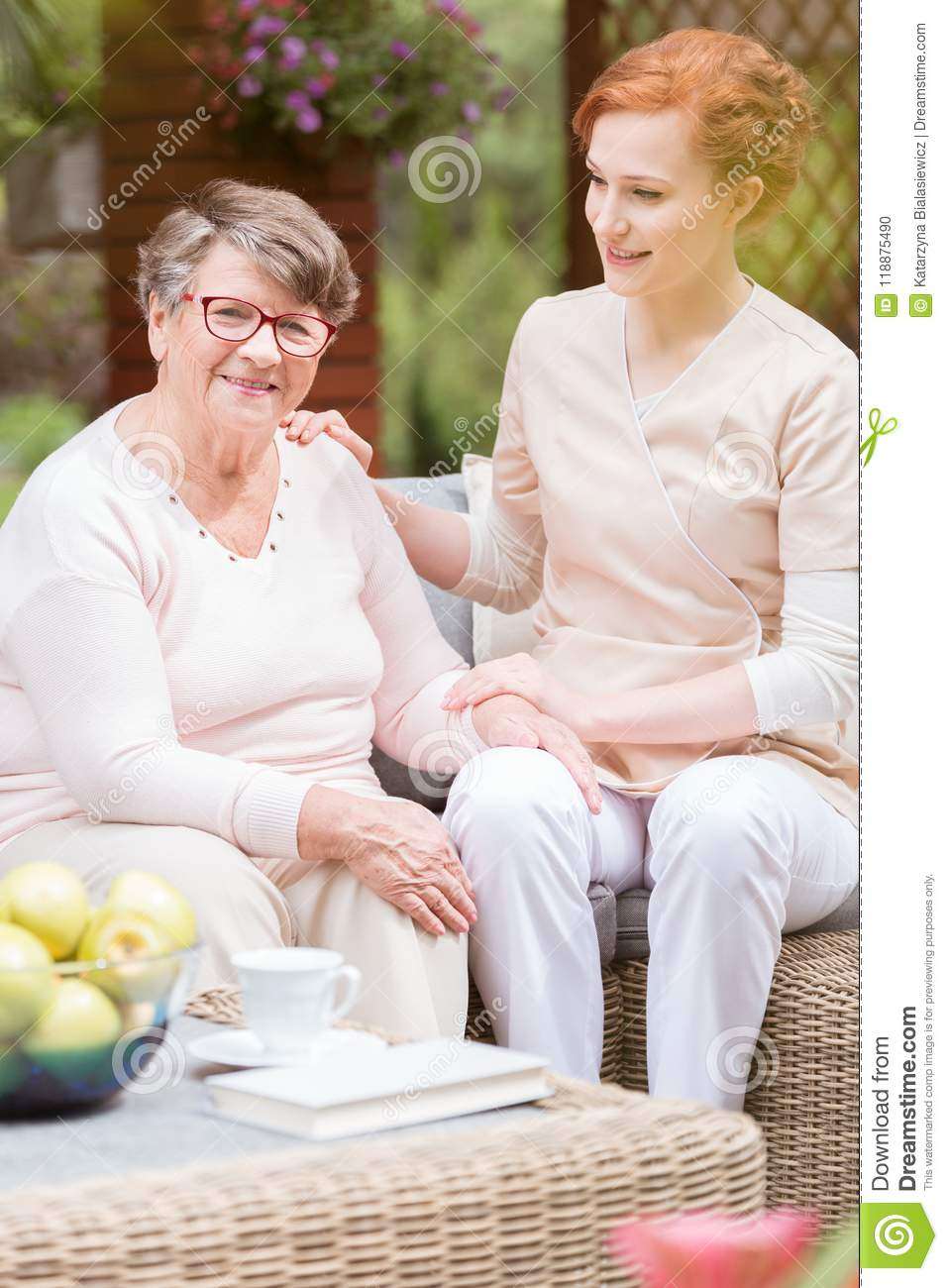 Tender professional caregiver in uniform putting her hand on a s