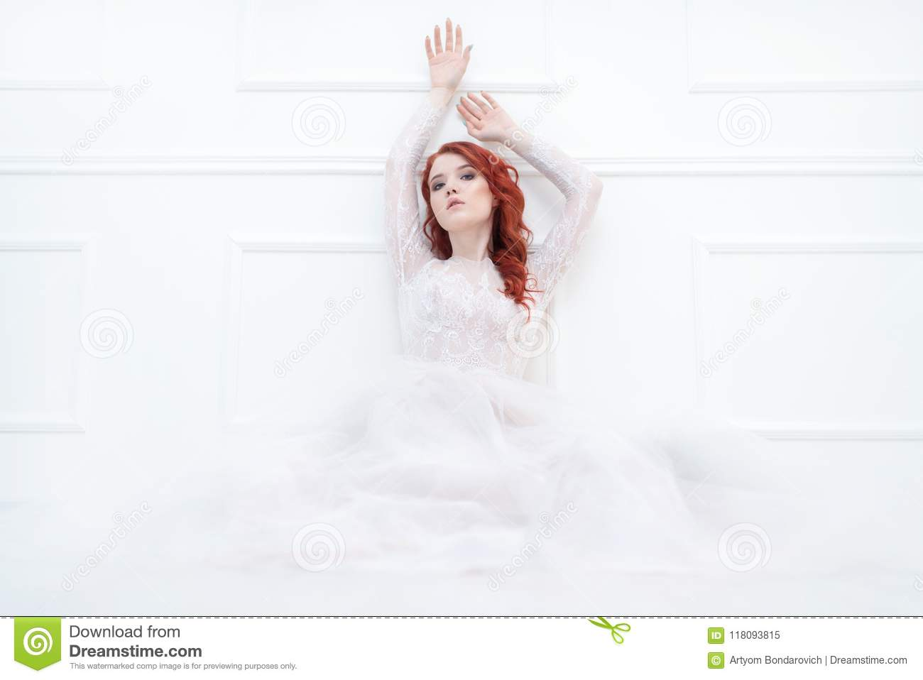Tender retro portrait of a young beautiful dreamy redhead woman in beautiful white dress.
