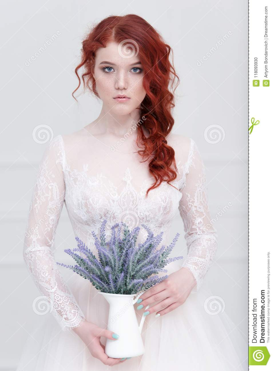 Tender retro portrait of a young beautiful dreamy redhead woman in beautiful white dress with bouquet of lavender.