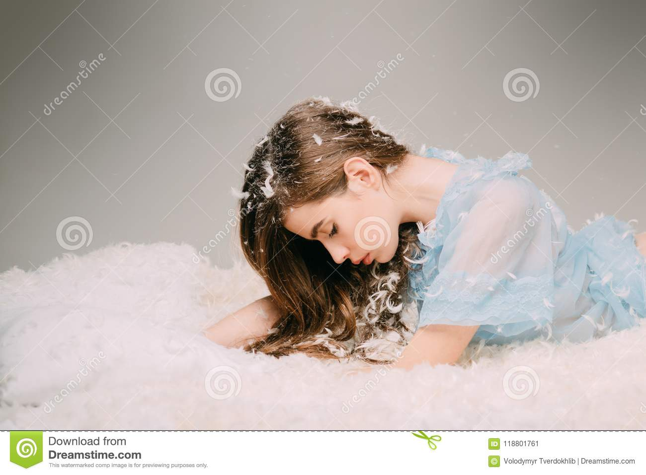 Tenderness and fragility of youth concept. Side view teenage girl lying on drowsy bed on gray background. Beautiful