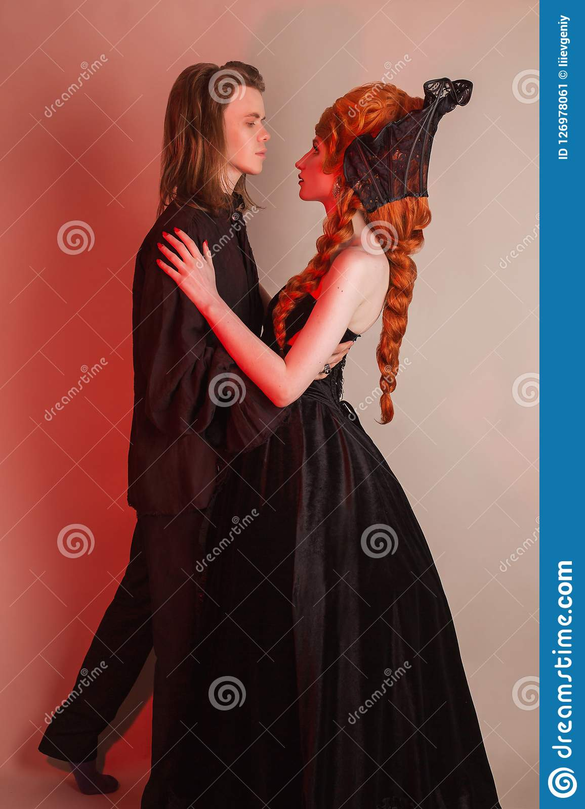 Tenderness in a relationship. Gothic couple dancing in halloween clothes. Redhead woman in dress. Vampire couple on dark backgroun