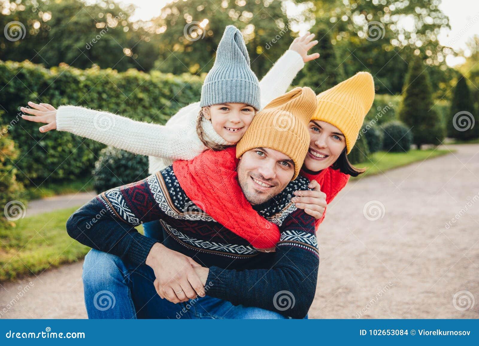Tendo o tempo agradável junto! A mulher entusiasmado de sorriso, o homem e sua criança fêmea pequena, vestem a roupa feita malha