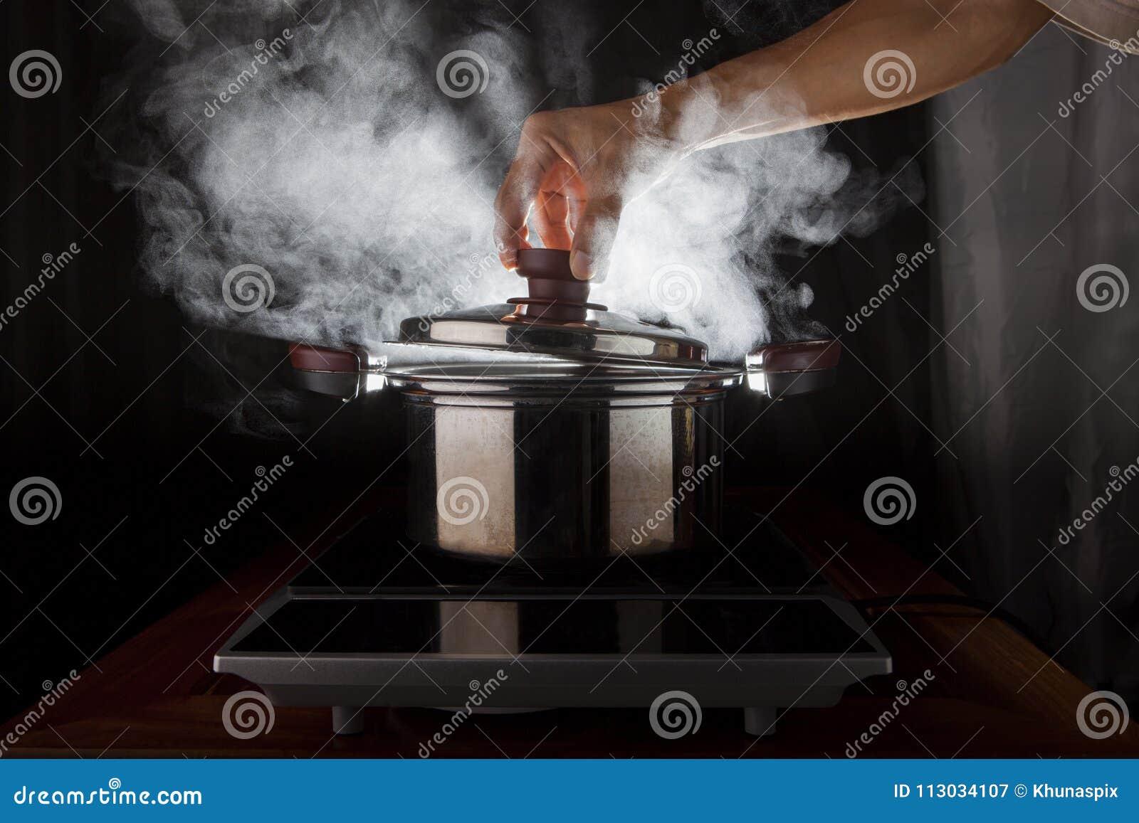 Tenencia de la mano de la cubierta del pote del metal con el vapor caliente que fluye de insi