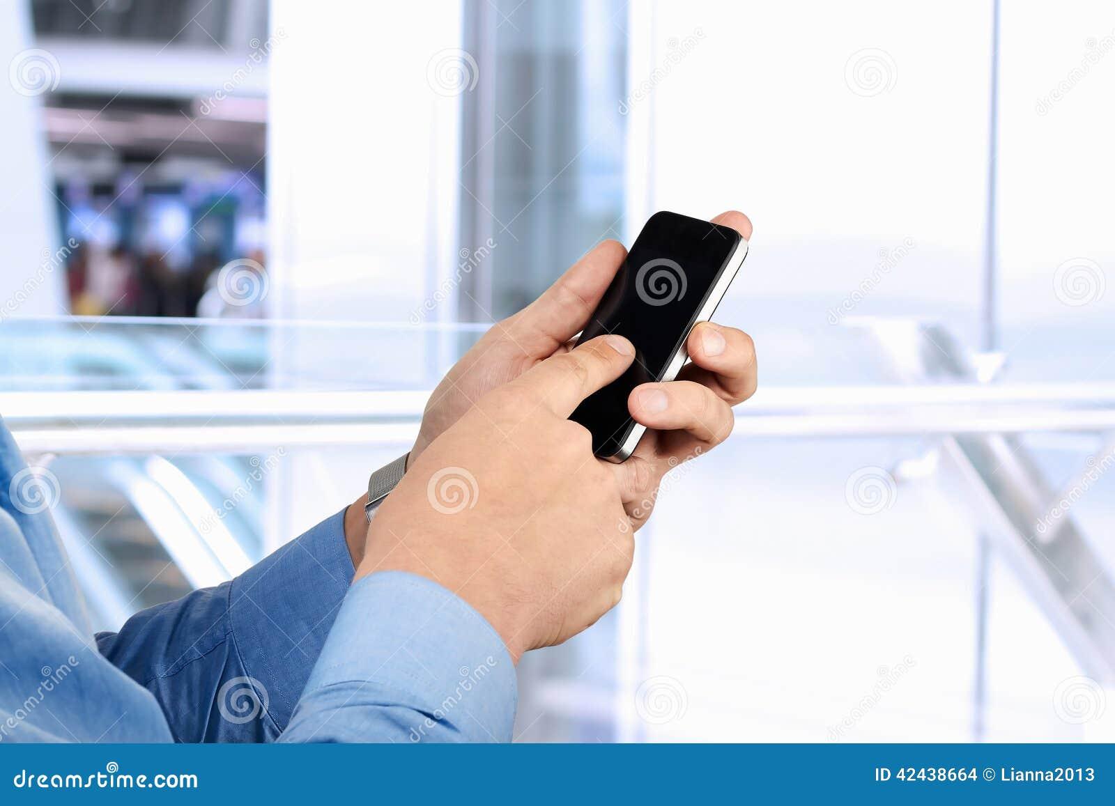 Tenencia del hombre de negocios y usar un teléfono elegante móvil