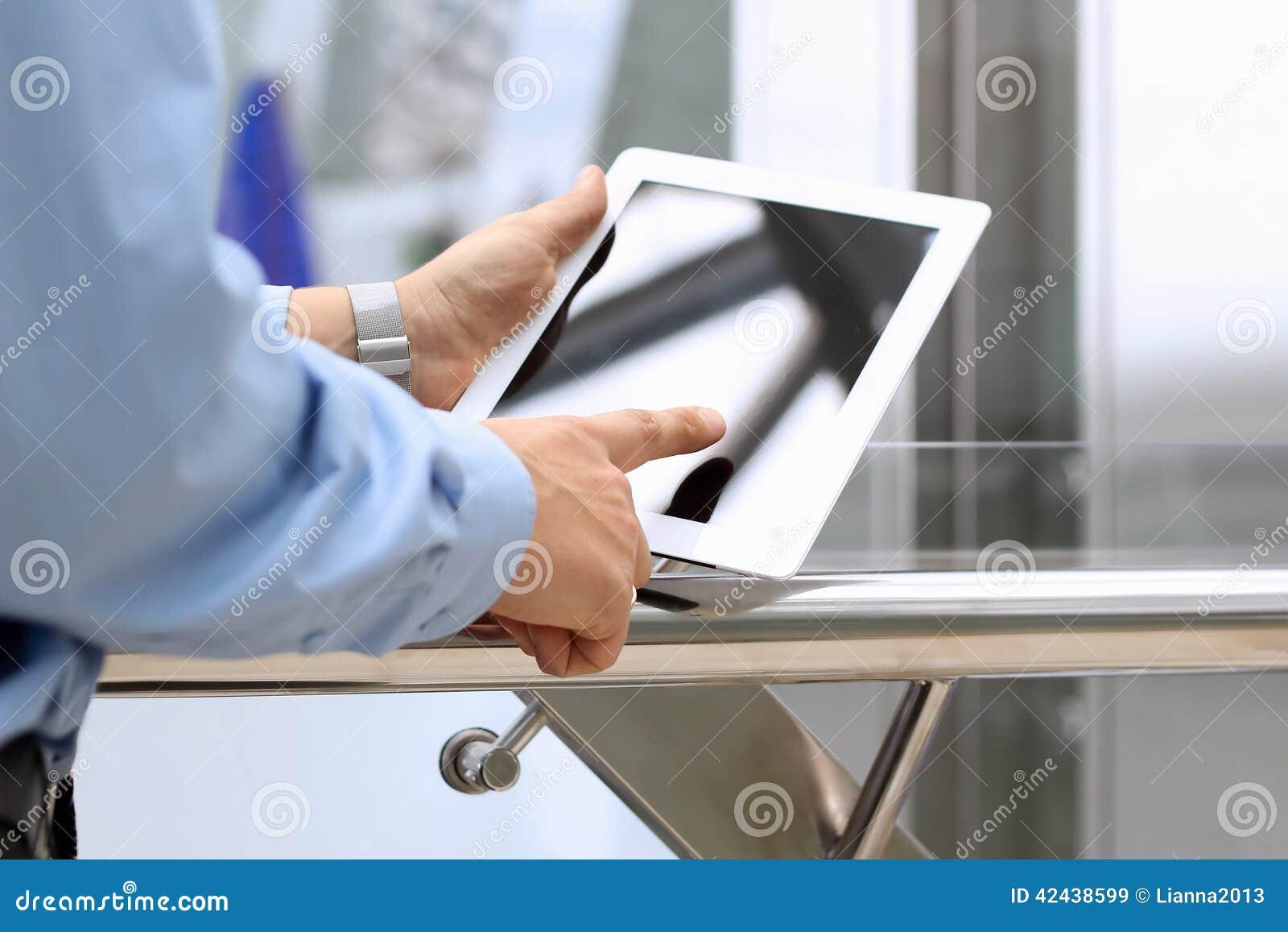Tenencia del hombre de negocios y usar una tableta digital