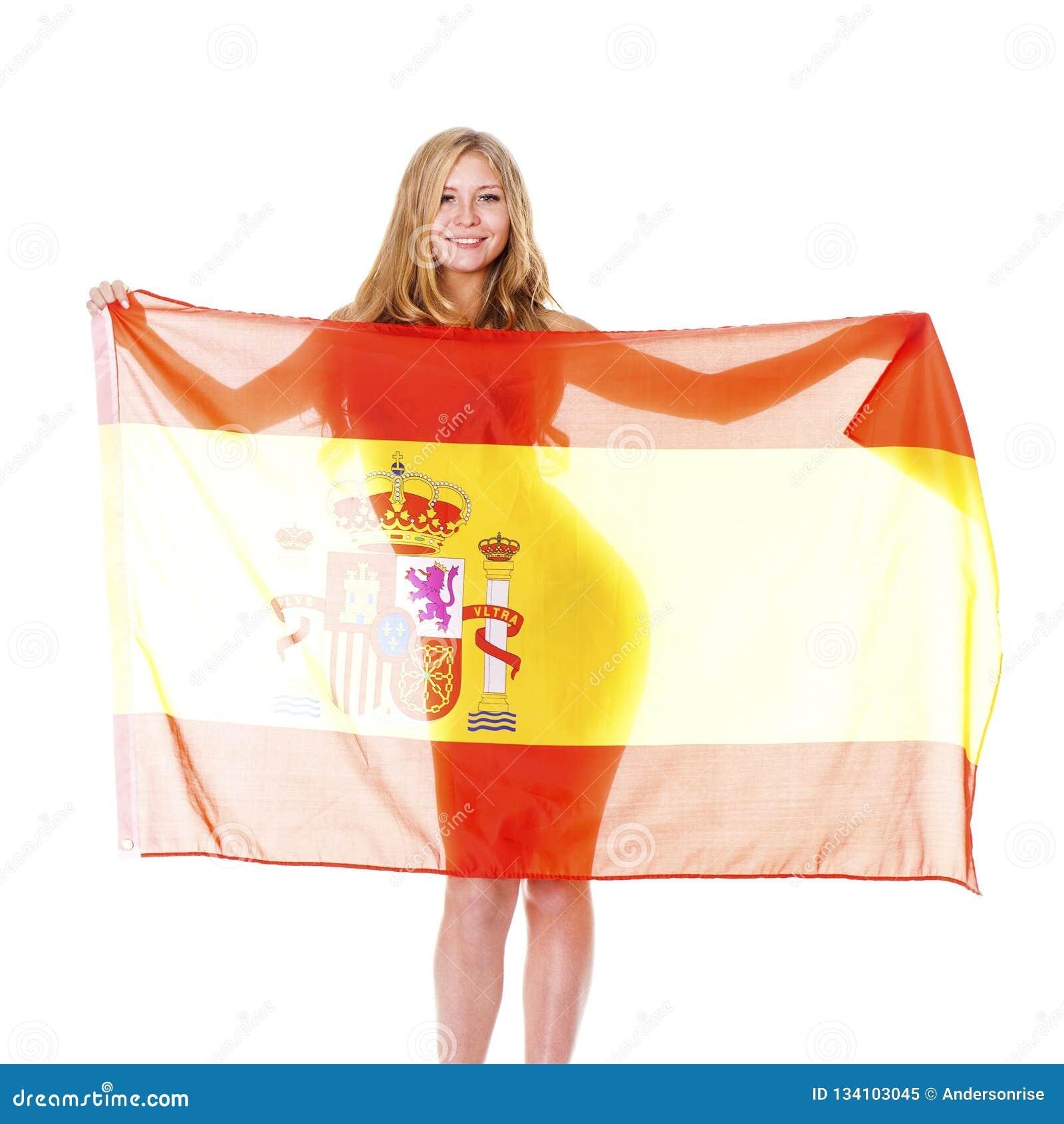 Tenencia rubia feliz joven una bandera española aislada en el fondo blanco