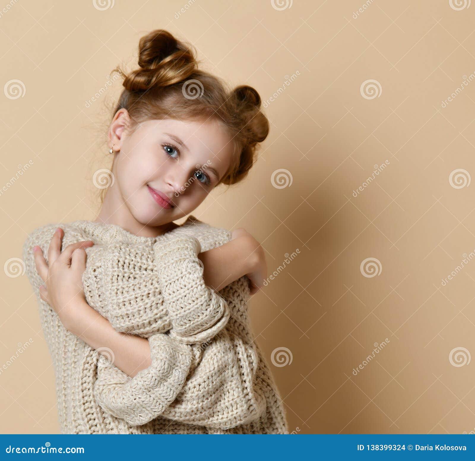 Tenencia sonriente de la muchacha del retrato ascendente cercano que se abraza fondo desnudo aislado de la pared