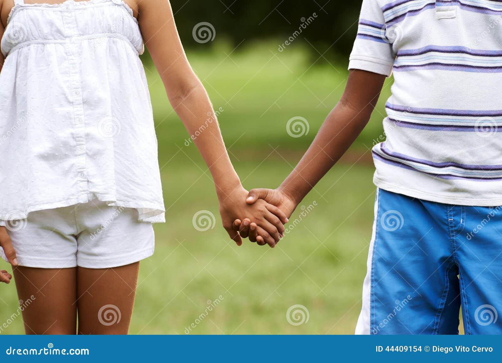 Tenersi per mano bianco della ragazza del ragazzo del nero di amore dei bambini