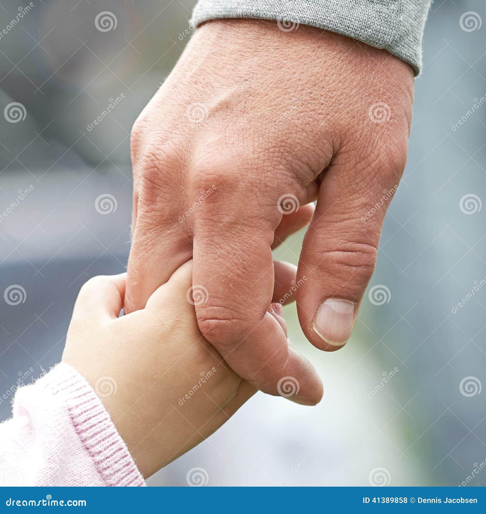 Tenersi per mano del genitore e del bambino
