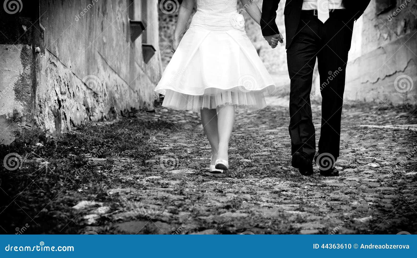 Tenersi per mano di camminata dello sposo & della sposa