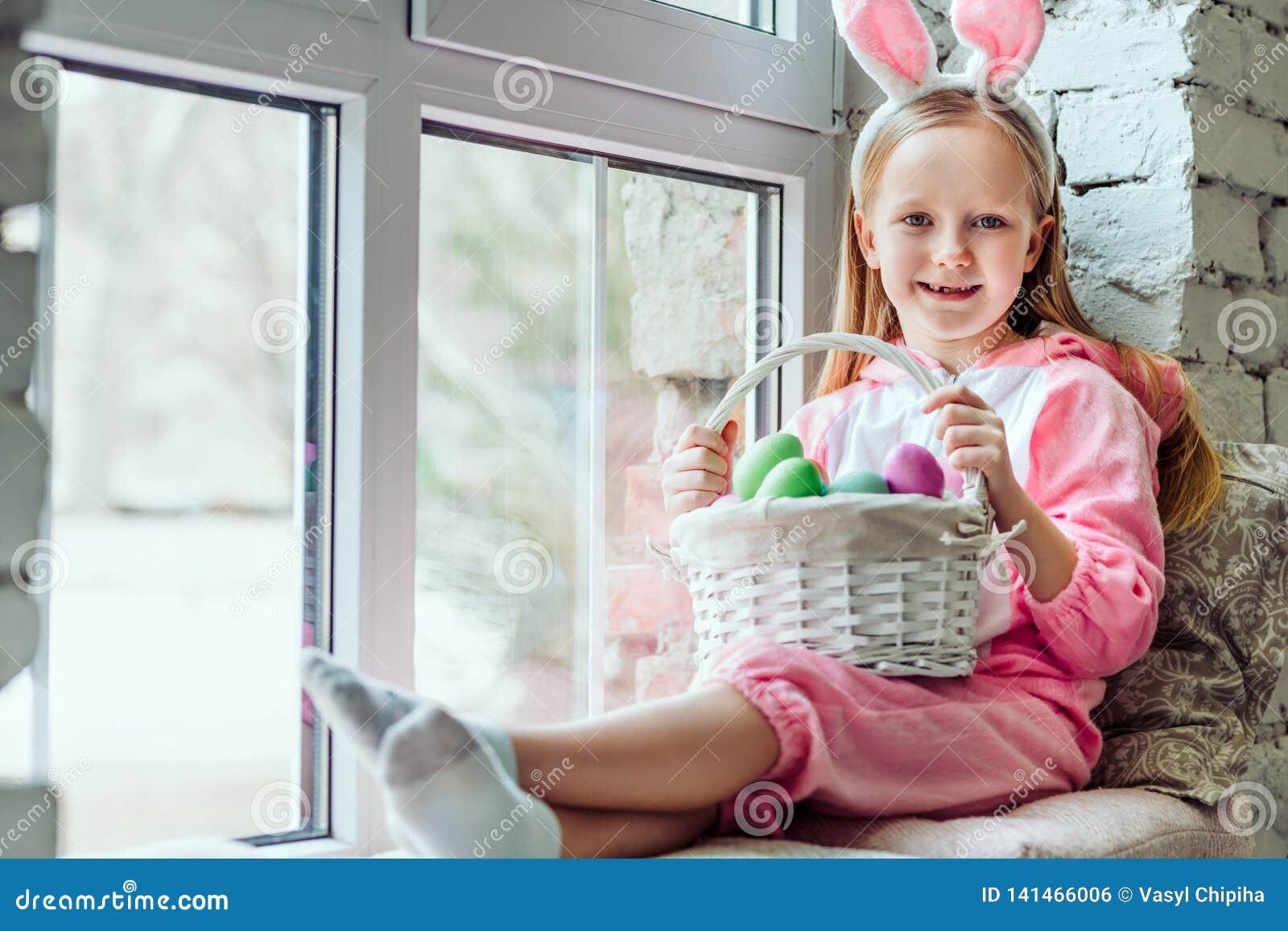 Tengo un humor de pascua La niña hermosa en un traje del conejo se está sentando en casa en el alféizar y está sosteniendo una ce