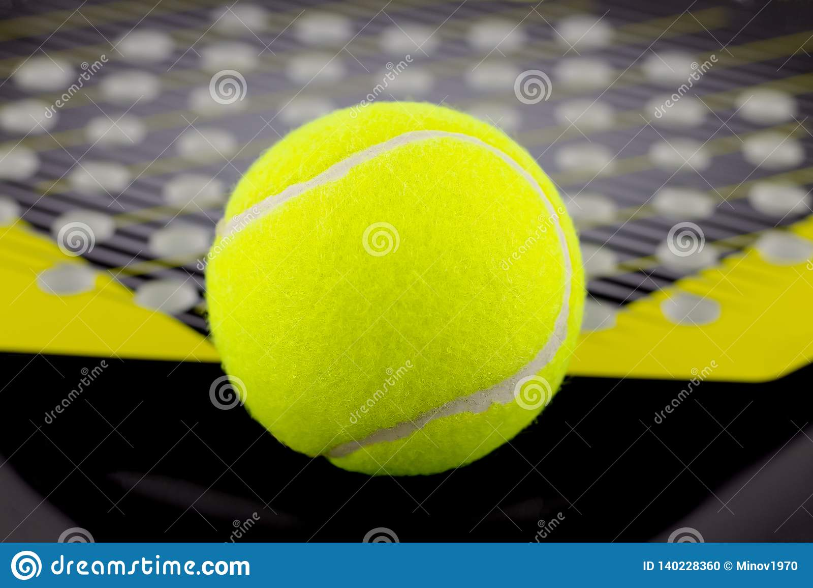 The tennis ball lies on a racket for playing beach tennis