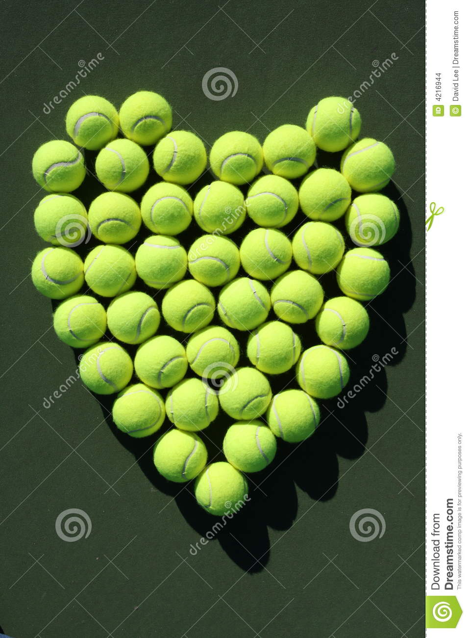 The shape of heart made of tennis balls arranged on dark green ...