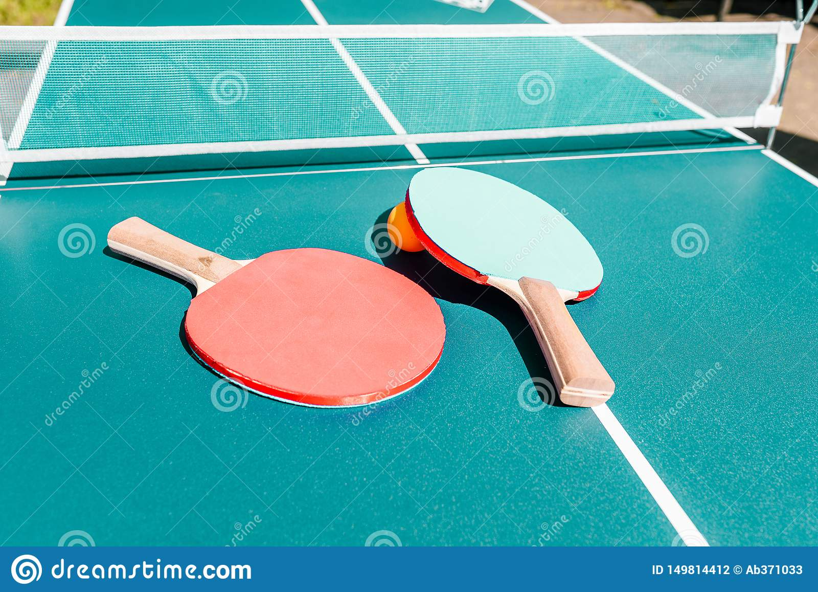 Tennis table with rackets. Bright green table with orange ball and white net. Activities and sports. Banner in a sports shop. The